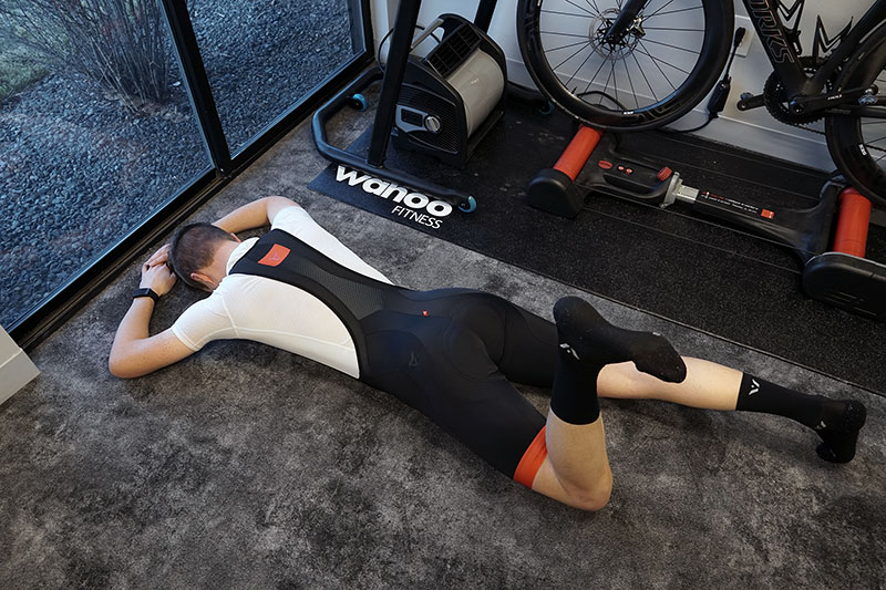 A man is lying on his stomach completing an exercise for glute activation for cycling.