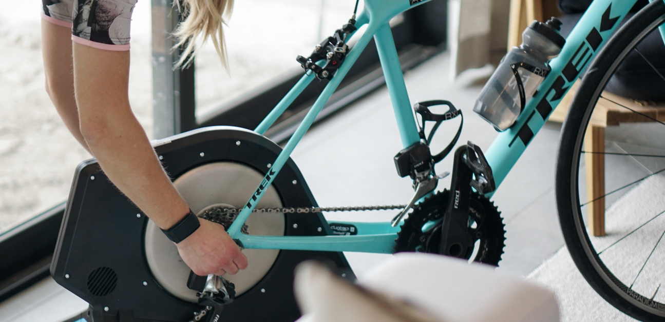 A beginner rider places her bike on an indoor trainer