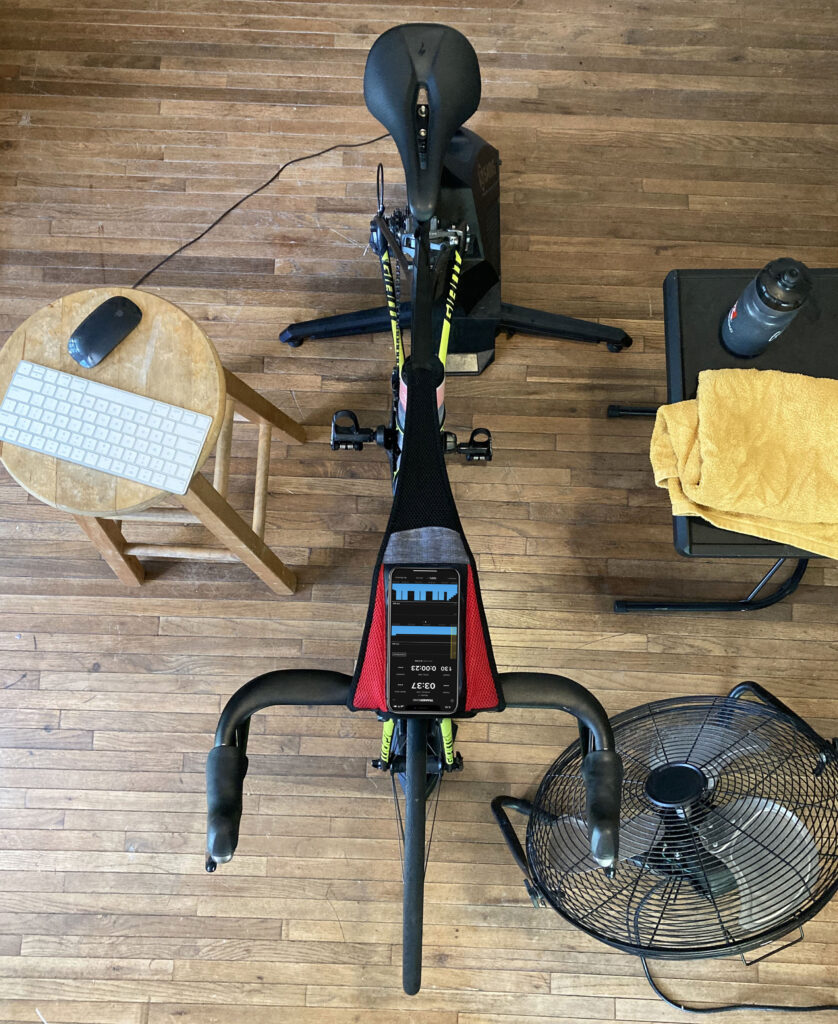 an indoor training setup including bike, indoor trainer, towel, and hydration