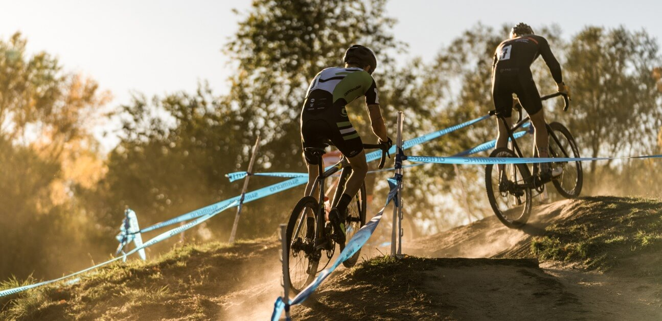 A cyclocross racer rides up a hill