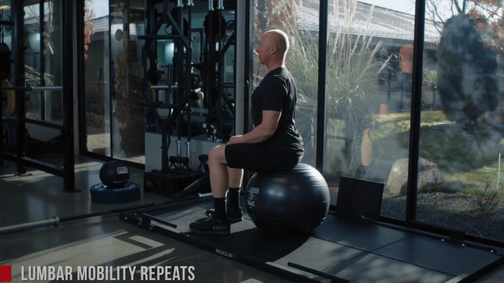 Chad sits on an ab ball with an over-extended lower back.