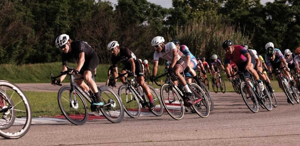 A fast-moving group of cyclists drafts one-another.