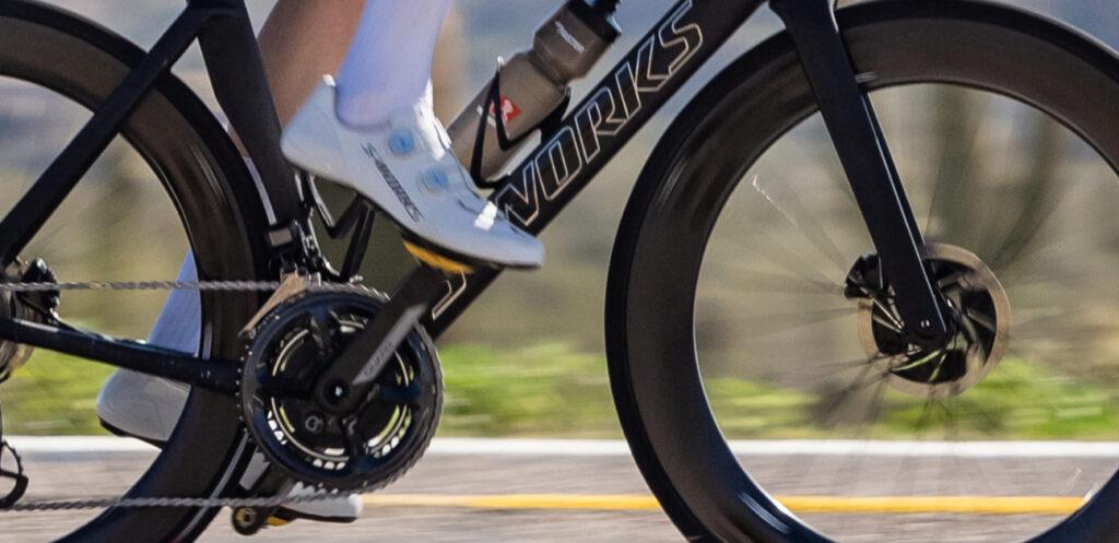 A cyclist rides on an expensive, aero-optimized bike.